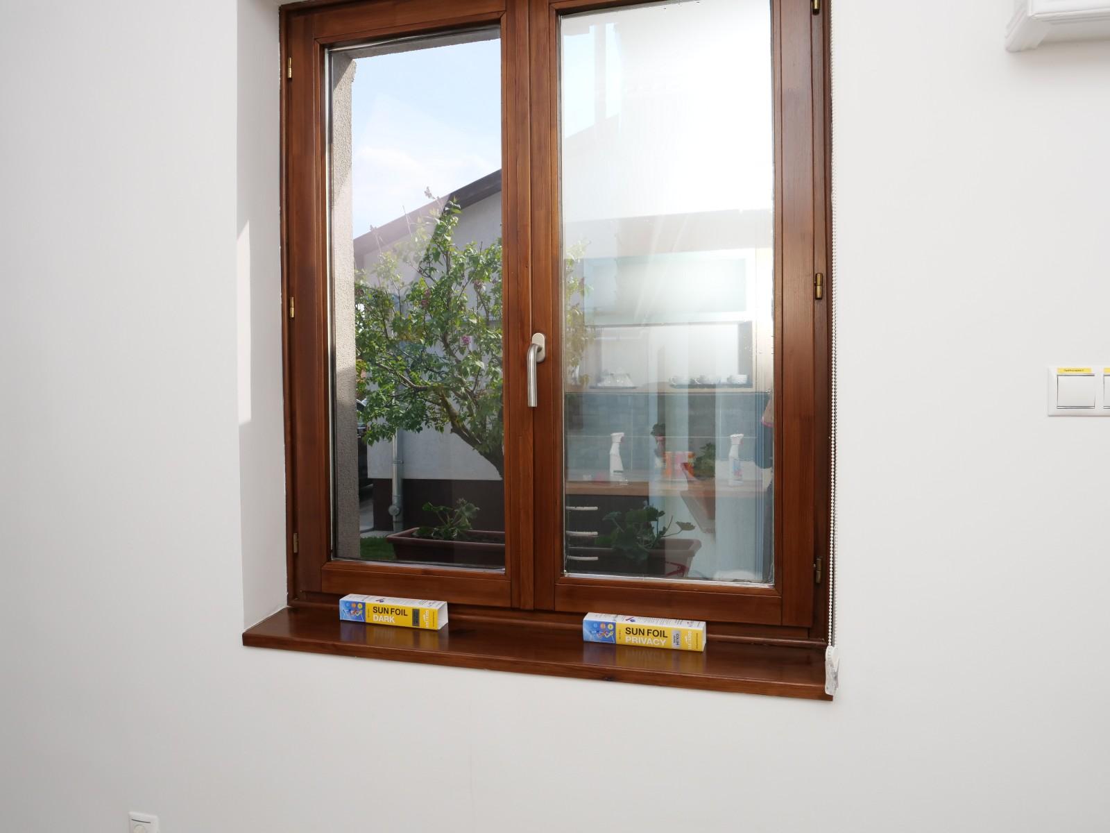 A napellenző ablakfólia a szobából kifelé nézve: a kilátást nem akadályozza, de látható, hogy sötétítette az ablak felületét, így kevesebb napfény tud besütni.