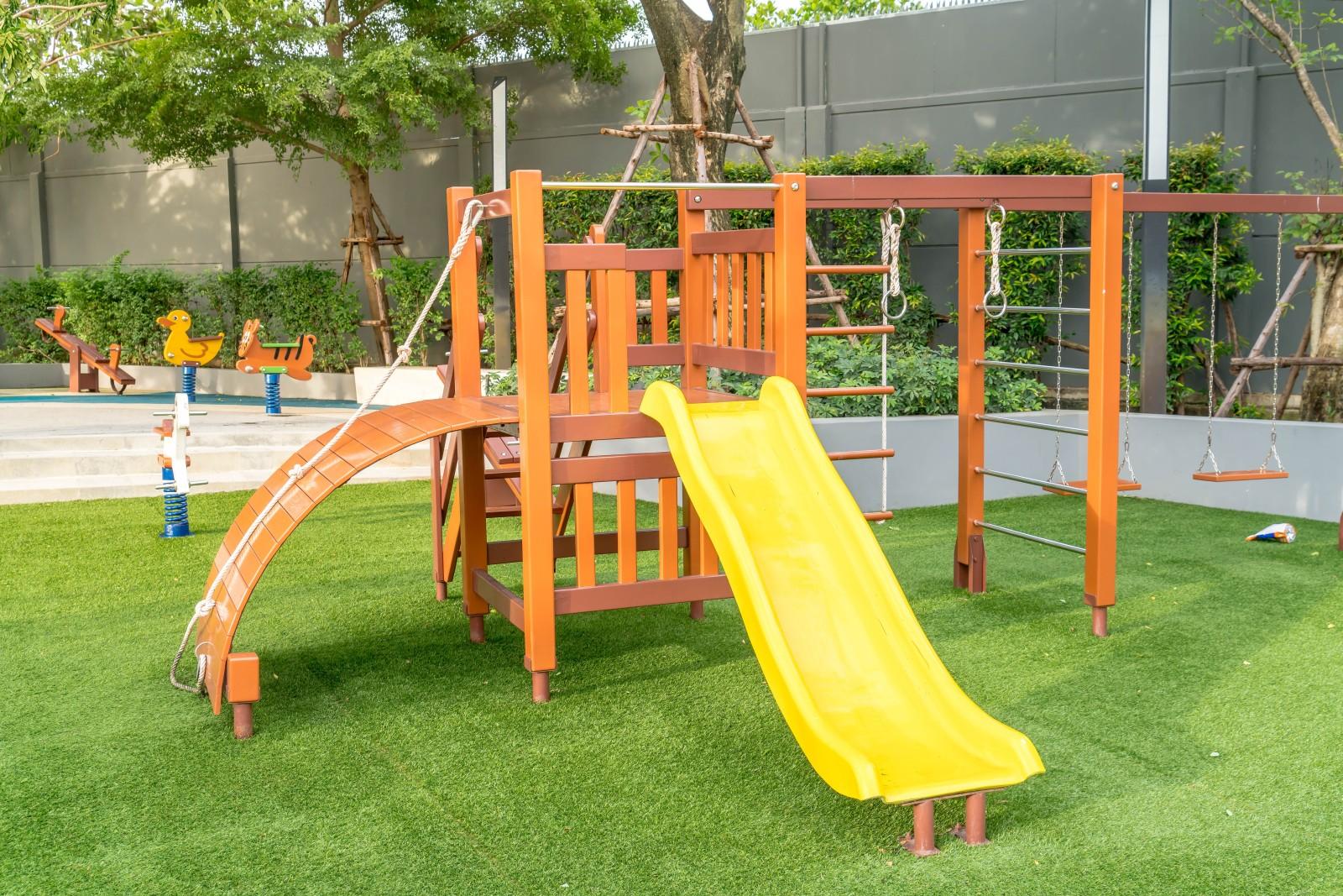 Egy kültéri játszótér esetében a műfű gondozásmentes és esztétikus burkolatot biztosít.