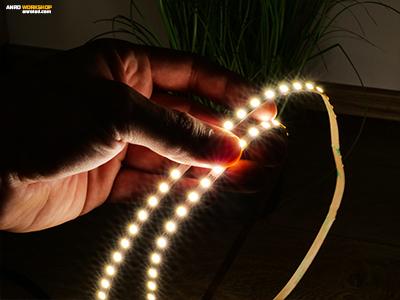 Keskeny, 5 mm széles LED szalag kézben tartva, bekapcsolva, így világít.