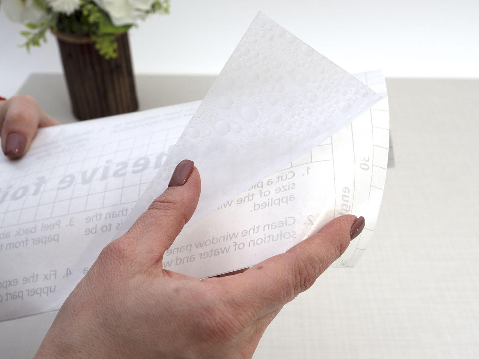 A vékony, áttetsző üvegfóliát felragasztás előtt egy védőpapír óvja a szennyeződésektől.