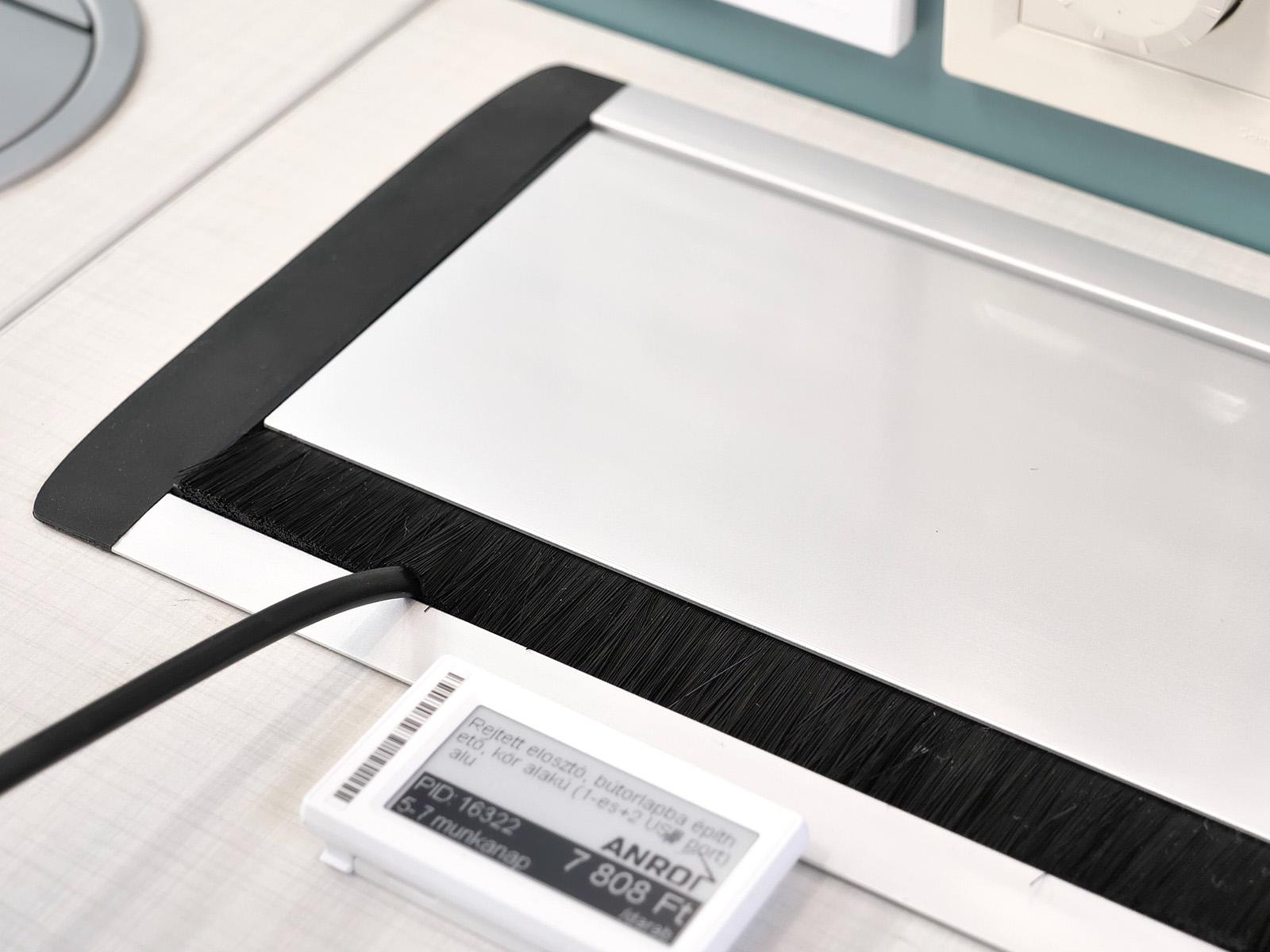 A kábelkivezetős típusnál a kábelek egy sörtén átvezetve szinte láthatatlanul csatlakoznak be az asztallap alá.