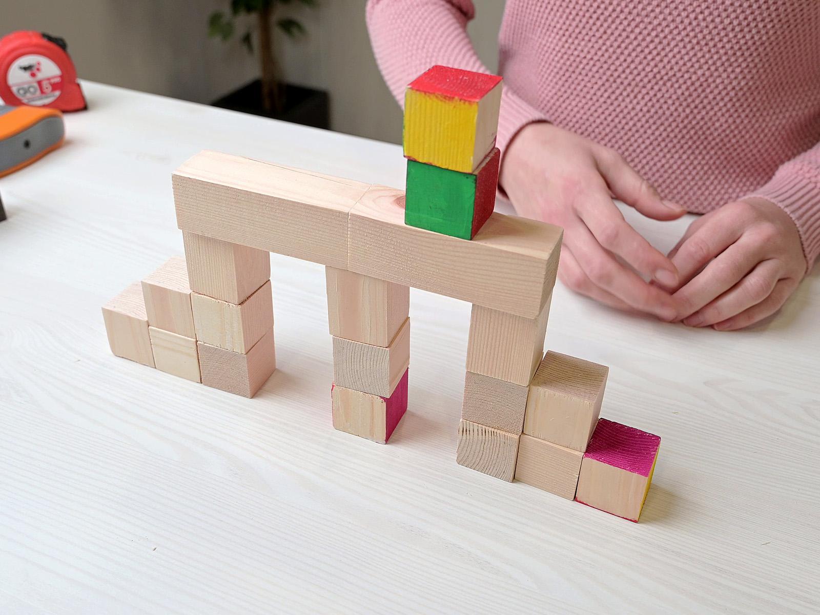 A natúr vagy színes kocka és hasáb formák egy építőjáték elemei is lehetnek.