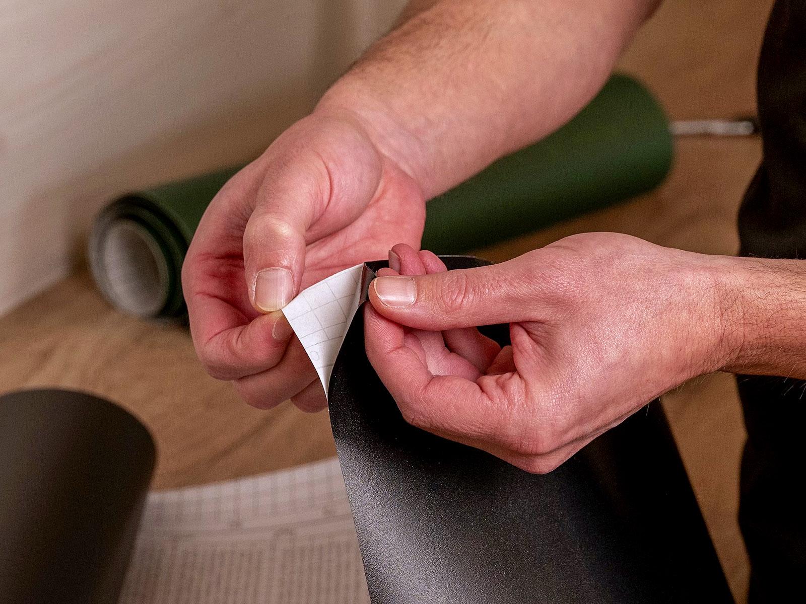 Az öntapadós fólia leválasztása a védőpapírról.