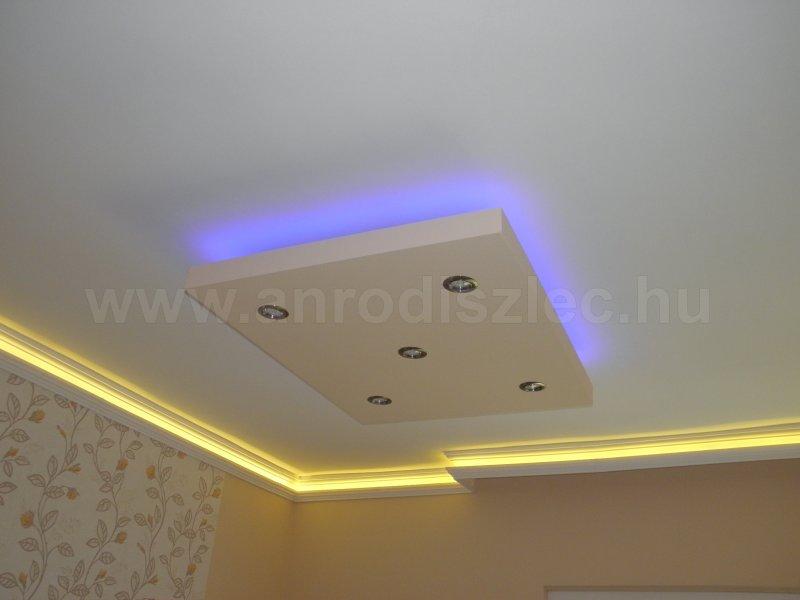 Nappali különböző hangulatvilágításokkal: oldalfalon melegfehér dekor szalag, középen színváltós szalaggal díszített álmenyó.