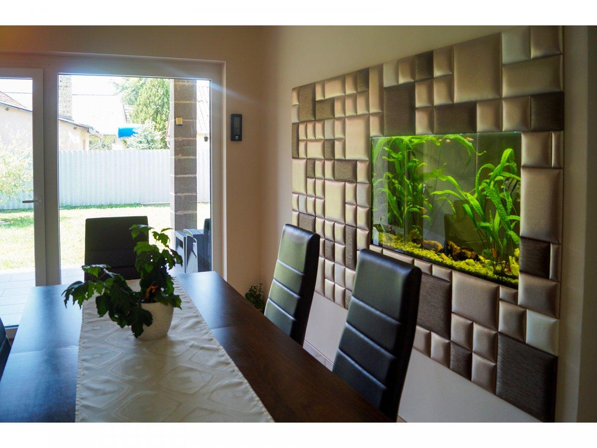 Az étkező falába épített akvárium környezete bézs, arany és barna bőrpanelekkel van díszítve.