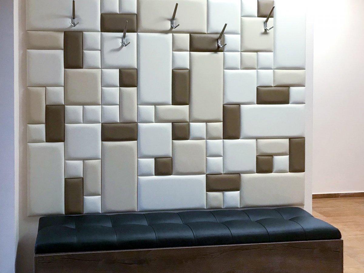 Az előszobában egyszerre díszítik és védik a falat a fogasok alá ragasztott műbőr bevonatos falpanelek.